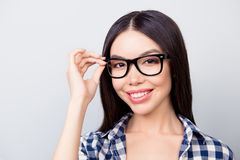 Close up portrait of charming smart lady with toothy smile, haze. L eyes and beautiful face is touching her spectacles, dressed in casual checkered clothes Royalty Free Stock Photography