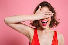 Close-up portrait of charming smiling brunette woman hiding eyes. Under hand, isolated on pink background Royalty Free Stock Image