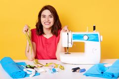 Close up portrait of charming woman seamstress sitting at table with sewing machine on yellow background in studio, dressmaker. Sews new dress, looks happy stock photos