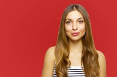 Close up portrait of charming young woman with gently smile posing over red background royalty free stock photos