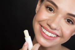 Positive girl is using hypoallergenic balm. Close up portrait of cheerful attractive young woman is looking at camera with joy while holding hygienic lipstick stock image