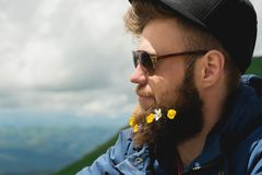 Close-up portrait of a cheerful bearded man in sunglasses and a gray cap with wildflowers in a beard. Soft brutality and. Good masculinity stock images