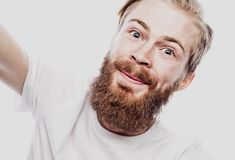 Close up portrait of a cheerful bearded man taking selfie over white background. Studio shoot stock images