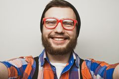 Close up portrait of a cheerful bearded man taking selfie over white background. Studio shoot stock image
