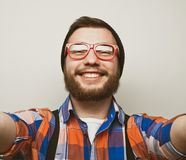 Close up portrait of a cheerful bearded man taking selfie over white background. Studio shoot stock photo