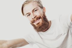 Close up portrait of a cheerful bearded man taking selfie over white background. Studio shoot royalty free stock photos