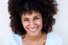 Portrait of cheerful beautiful woman with curly hair by white wall Stock Image