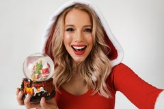Close up portrait of a cheerful blonde woman. Dressed in red New Year costume standing over white background, holding snowball, taking a selfie stock photo