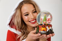 Close up portrait of a cheerful blonde woman. Dressed in red New Year costume standing over white background, holding snowball stock photography