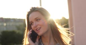 Close-up portrait of a cheerful lady talking on the phone and walking down the street with a smile on her face, sunlight stock video footage