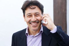 Close up cheerful mid adult businessman talking on mobile phone. Close up portrait of cheerful mid adult businessman talking on mobile phone Royalty Free Stock Photo