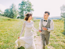 The close-up portrait of the cheerful newlyweds holding hands while running in the countryside. stock photography
