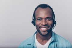 Close up portrait of cheerful positive smart clever friendly guy. Wearing casual clothing using headphones for working isolated on gray background, always ready Royalty Free Stock Image