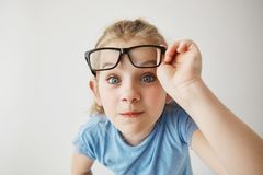 Close up portrait of cheerful small girl with blonde hair and blue eyes funny imitates adult person with glasses with. Surprised expression Stock Photos