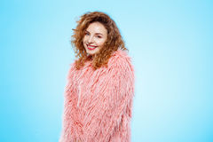 Close up portrait of cheerful smiling beautiful brunette curly girl in pink fur coat over blue background. Royalty Free Stock Photo