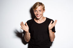 Close up portrait of cheerful smiling blond handsome young man wearing black t-shirt clapping hands isolated on white. Close up portrait of smiling blond Stock Photography
