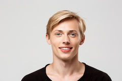 Close up portrait of cheerful smiling blond handsome young man wearing black t-shirt isolated on grey background Royalty Free Stock Photo