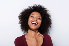 Close up cheerful young african woman with hand in hair and laughing royalty free stock images
