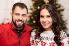 Happy couple at christmastime. Close-up portrait of cheerful young couple smiling at camera at christmastime royalty free stock images