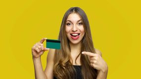 Close up portrait of cheerful young girl with long hair showing and pointing finger credit card isolated over yellow background stock image