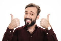 Close up portrait of a cheerful young man. Showing two thumbs up isolated over white background Stock Photography