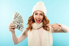 Close up portrait of a cheery pretty girl. Dressed in hat and scarf pointing finger at bunch of money banknotes and looking at camera isolated over blue Stock Photography
