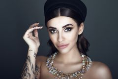 Glam dark-haired tattooed model with beautiful make up and smooth hair wearing black pillbox hat and luxurious gem necklace. Close up portrait of chic glam dark royalty free stock image