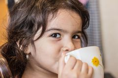 Little girl drinks from a mug of tea or juice. child nutrition issues. royalty free stock photos