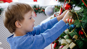 Close-up portrait of child decorating Christmas tree, closeup. Close-up portrait of child decorating Christmas tree. Little cute boy hanging a toy on the Royalty Free Stock Photo