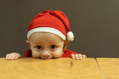 Close up portrait of child in santa hat licking table royalty free stock photo