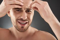 Close up portrait of concentrated frowning young bearded man plucking his eyebrows stock image