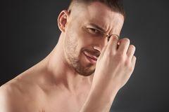 Close up portrait of concentrated young bearded man plucking his eyebrows royalty free stock image