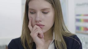 Close up portrait of concerned sad young lady in formal clothes looking away and in the camera, thinking about her stock video footage