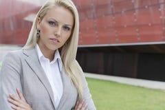 Close-up portrait of confident businesswoman against office building Stock Images