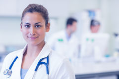 Close up portrait of confident female doctor at medical office. Close up portrait of a confident female doctor with colleagues in background at medical office Stock Images