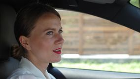 Portrait of woman talking on speakerphone in car. Close-up portrait of confident female driving car through modern cottage town and chatting by phone using stock video footage