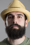 Close up portrait of confident proud hipster wearing straw hat looking at camera Stock Image