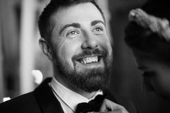 Close up portrait of a confident young man with beard smiling. bride groom straightens his tie. Close up portrait of a confident young men with beard smiling Royalty Free Stock Image