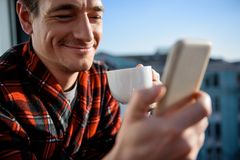 Happy adult male reading news in the morning on terrace. Close up portrait of contented guy looking at mobile phone with smile. He is having a cup of coffee and Stock Photos