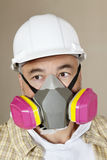 Close-up portrait of contractor with dust mask over colored background Stock Photos