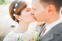 Close up portrait of couple against river and green trees. Beautiful young woman kissing handsome man outdoors Stock Photo