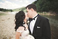Close up portrait of couple against river and green trees. Beautiful young woman kissing handsome man outdoors Royalty Free Stock Photos