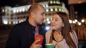 Close up portrait of couple drinking coffee at night. Stylish couple holding drinks talking with each other on city stock video footage