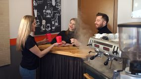 Portrait of a couple in a coffee shop behind the bar, Barista gives them coffee. stock video footage