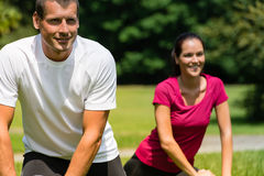 Close up portrait of couple stretching outdoors Stock Photo