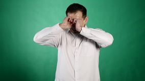 Close-up portrait of a crying man. A young businessman closes his aching eyes with tears on green background stock video