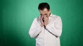 Close-up portrait of a crying man. A young businessman closes his aching eyes with tears on green background stock footage