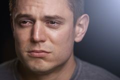 Close up portrait of crying young white man looking away royalty free stock photos