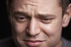 Close up portrait of crying young white man looking down stock images