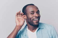 Close up portrait of curious interested delightful funny amazed. Cheerful surprised african man holding hand near ear and trying to hear the information Stock Photography